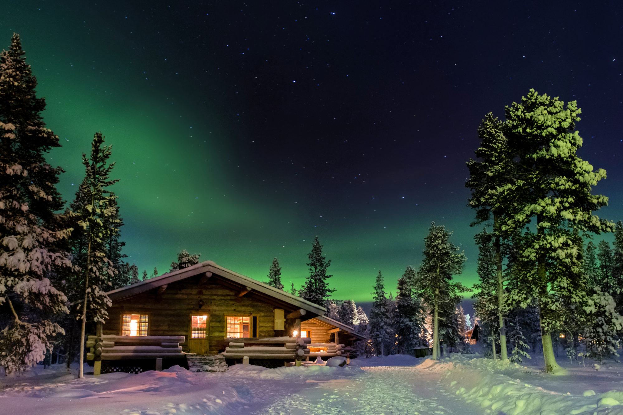 Aurora Borealis above cottages in Lapland.